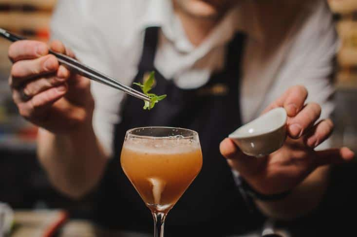 Bartender adding an ingredient into the cocktail