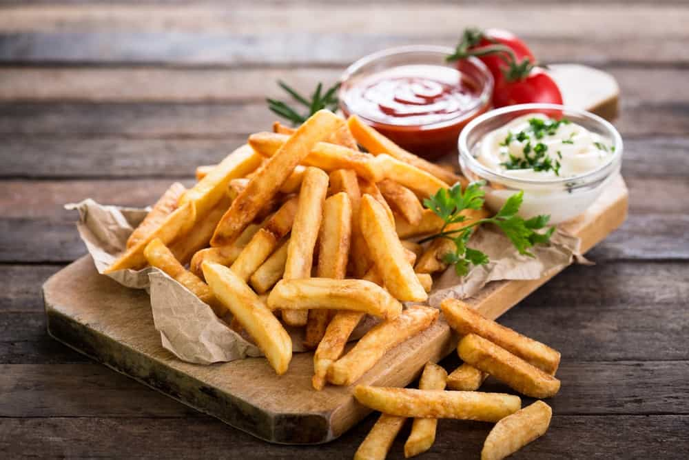 French fries on a wooden chopping board with ketchup and mayonnaise on the side.