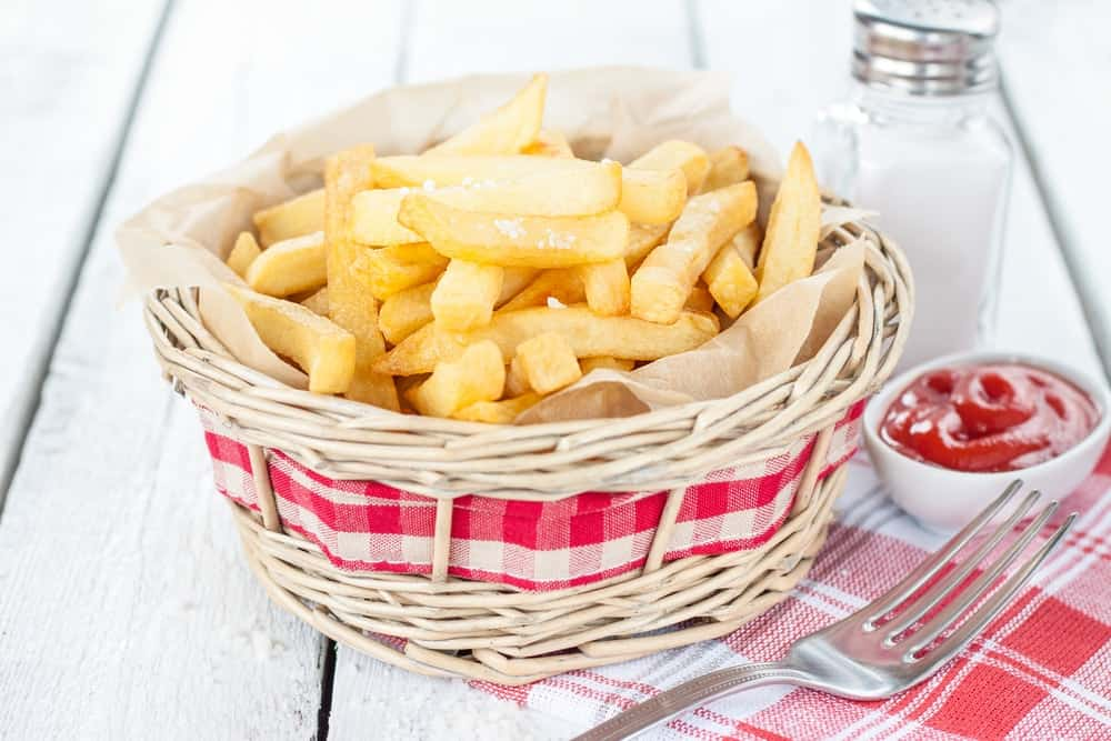 Bistro French fries in a wicker basket on white wood table with salt shaker and ketchup.