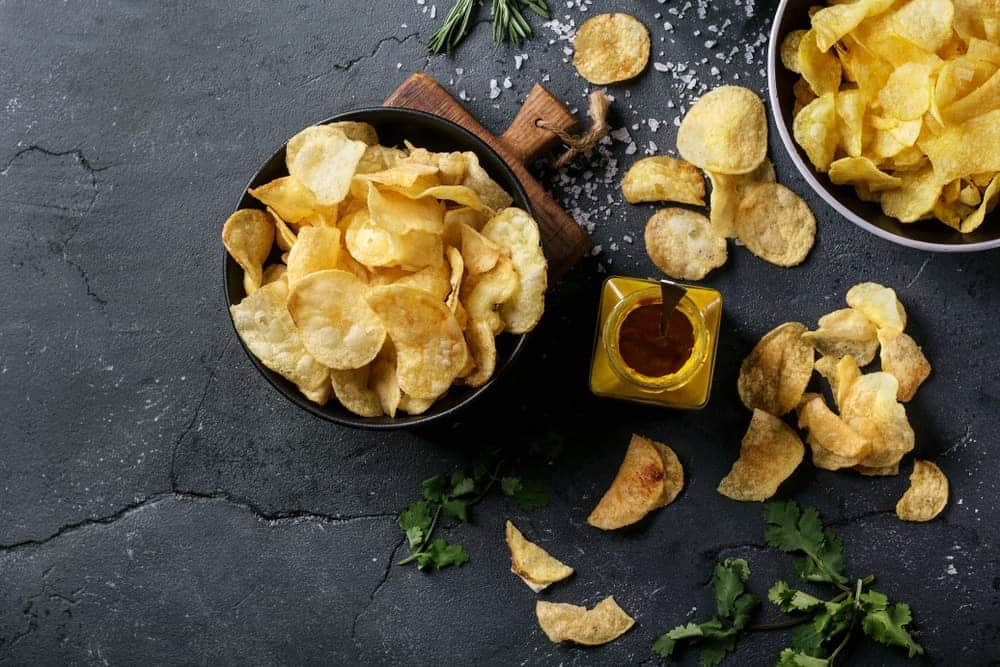 Bowl of home made potato chips served with mustard, rosemary, fleur de sel salt on stone background.