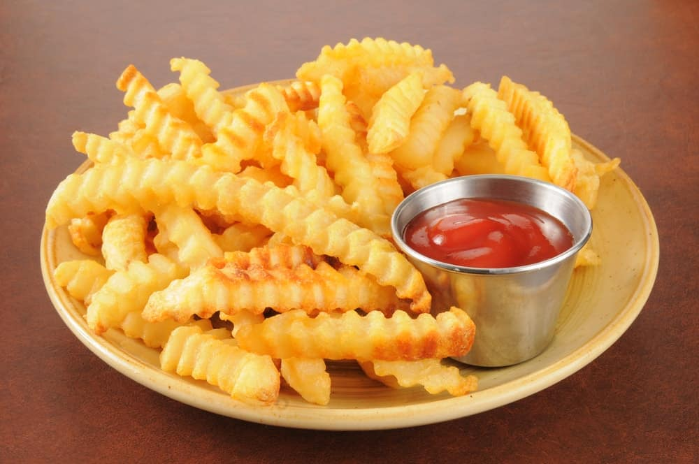 Crinkle cut french fries and a cup of ketchup on a plate.