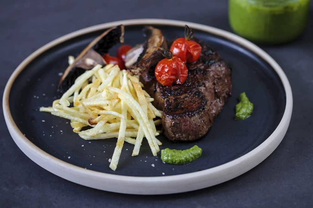 Fillet steak with roast tomatoes, matchstick fries and salsa verde.