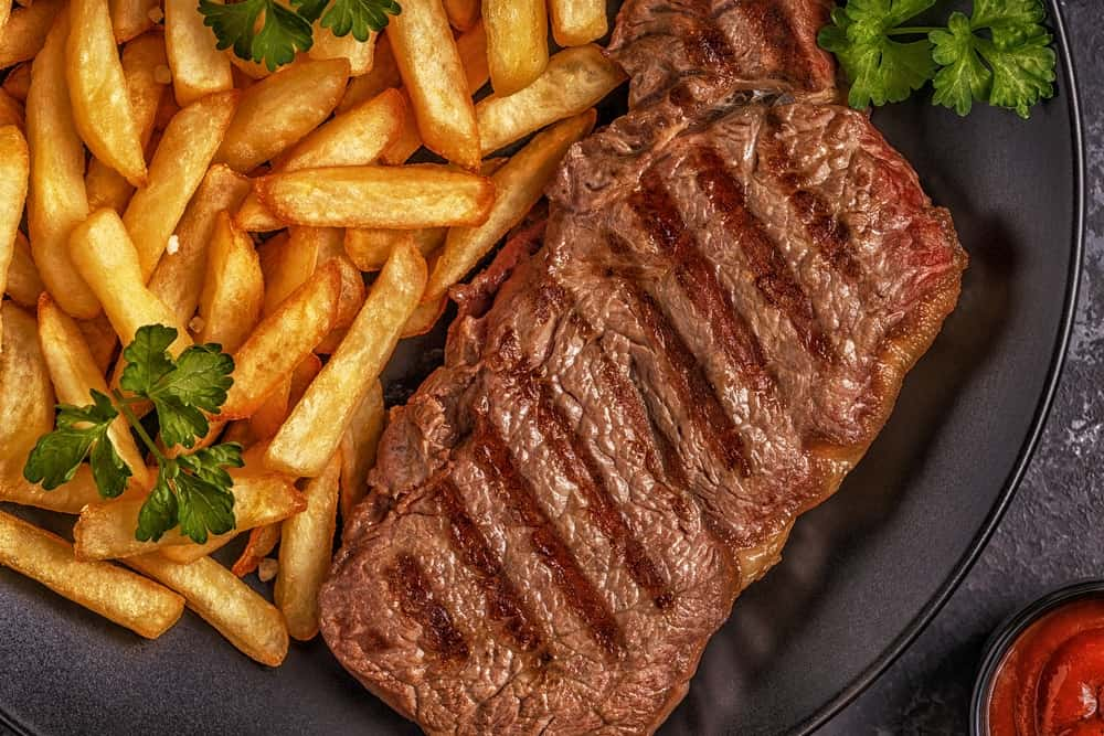 A juicy steak and its fries placed on a black plate with garnishes.