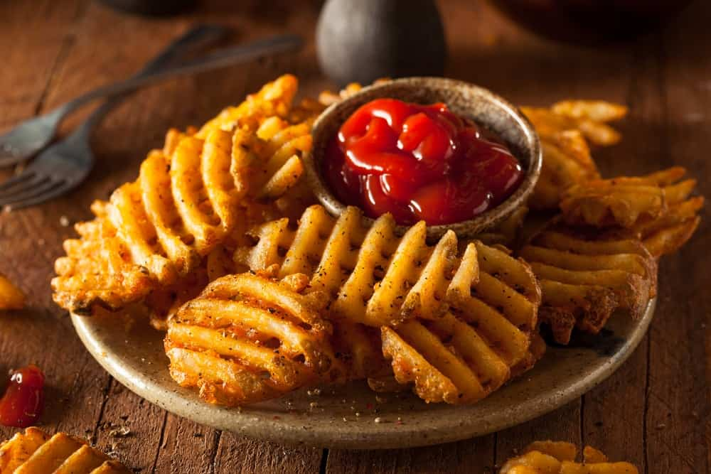 Crispy homemade waffle-cut fries with organic ketchup on a plate.