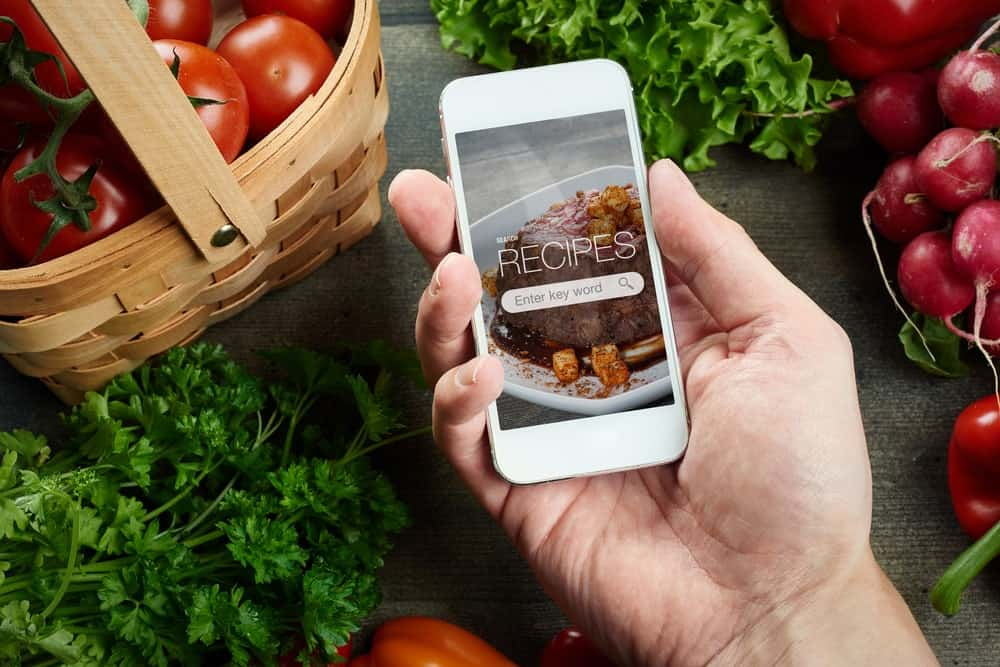 Hand holding a smartphone with a recipes mobile app on display and surrounded by fresh produce.