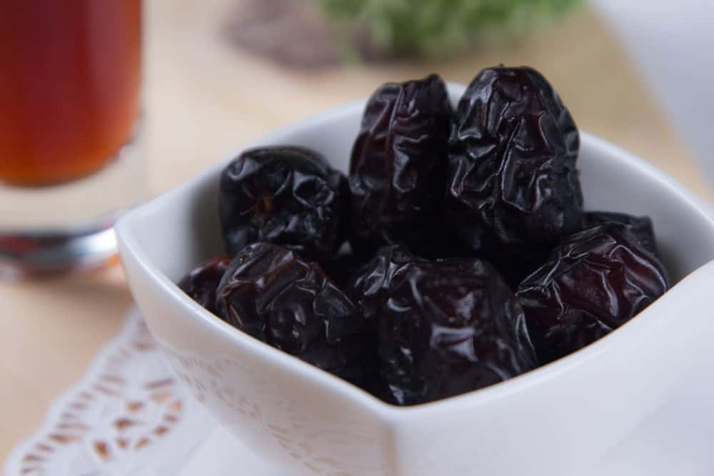 A bowl of Ajwa Dates ready to eat with a glass of sweet tea.