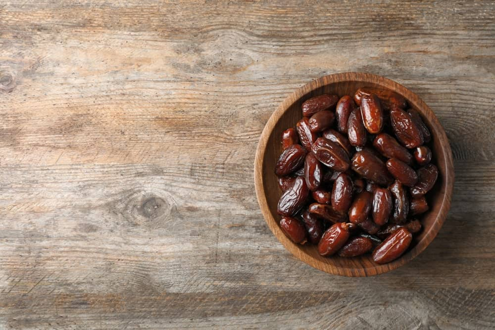 A wooden bowl filled with sweet Deglet Noor Dates.