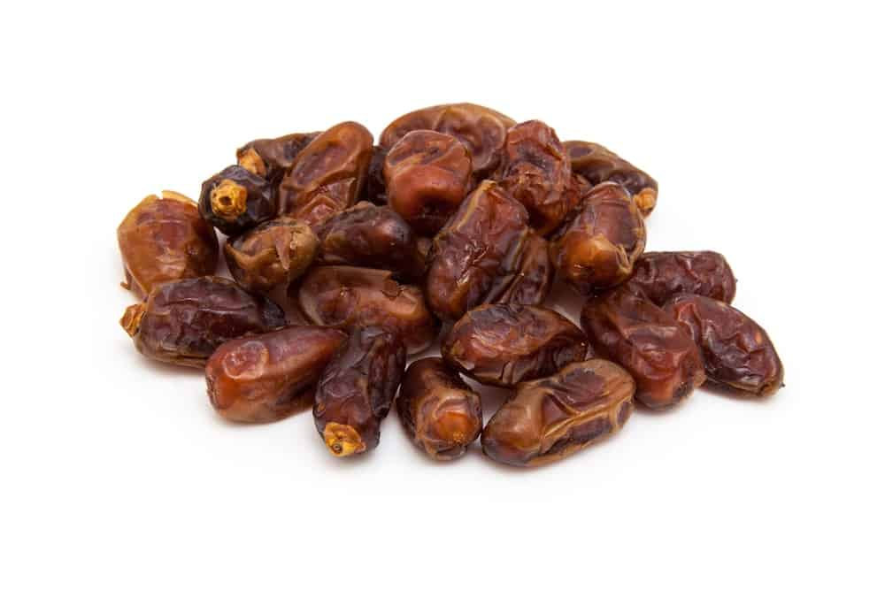 A bunch of dried Halawy Dates on a white background.
