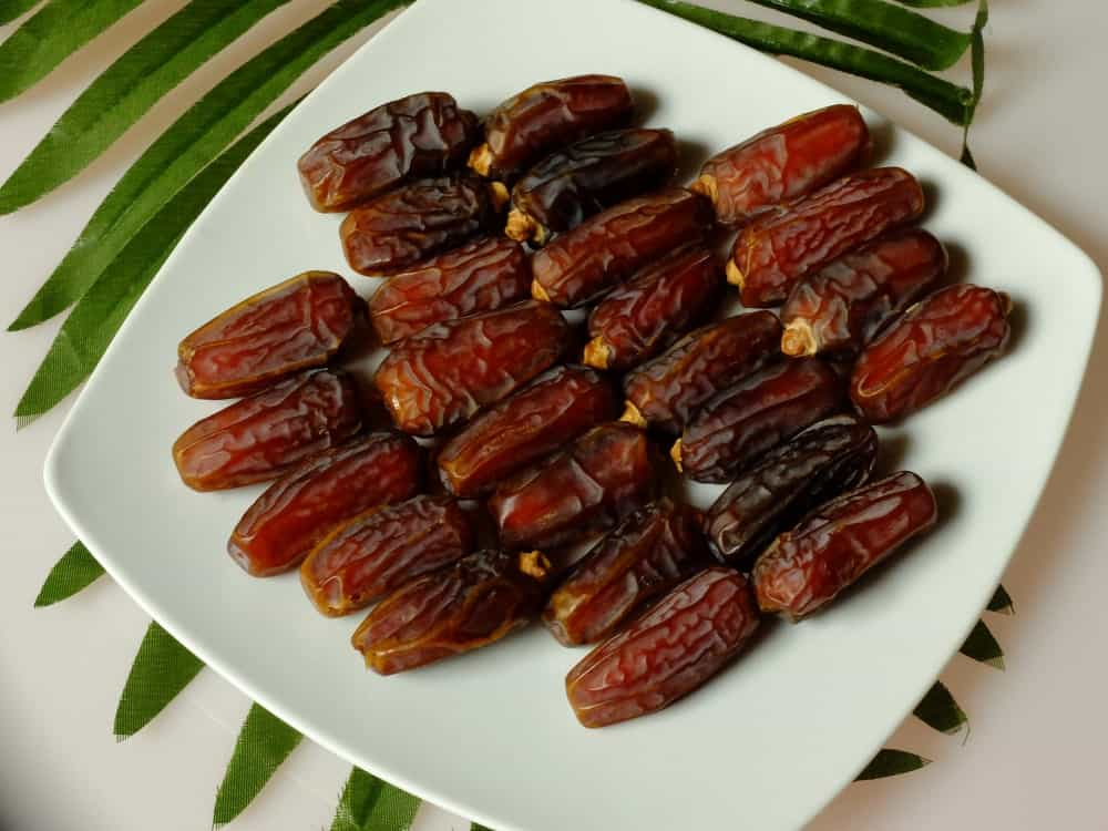 A plate of delicious Mabroom Dates on a white counter with palm leaves.