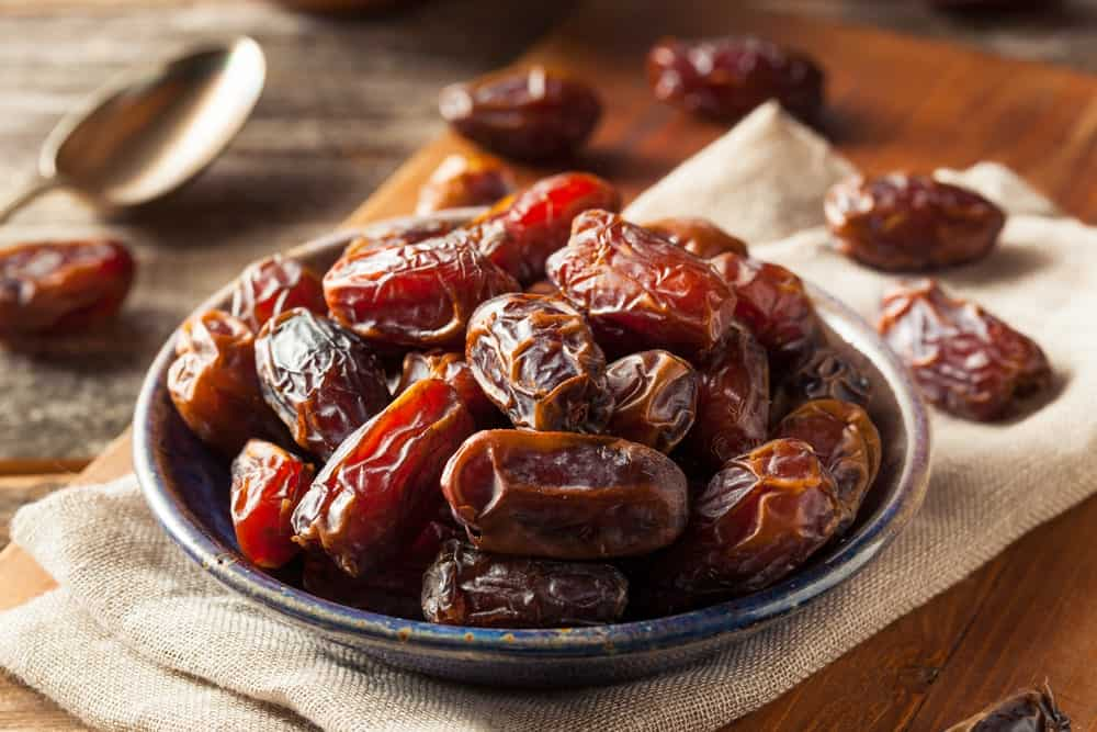 A small plate filled to the brim with rich and sweet Medjool Dates.