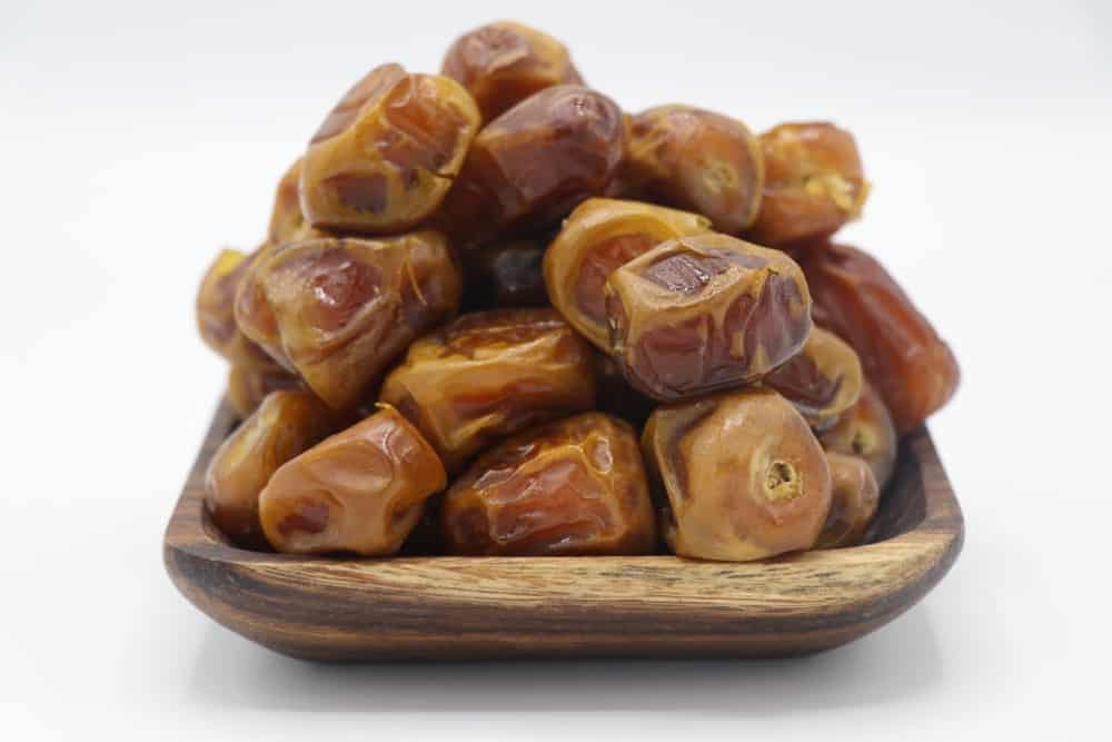A close-up look of a wooden plate filled with Sukkari Dates ready to eat.