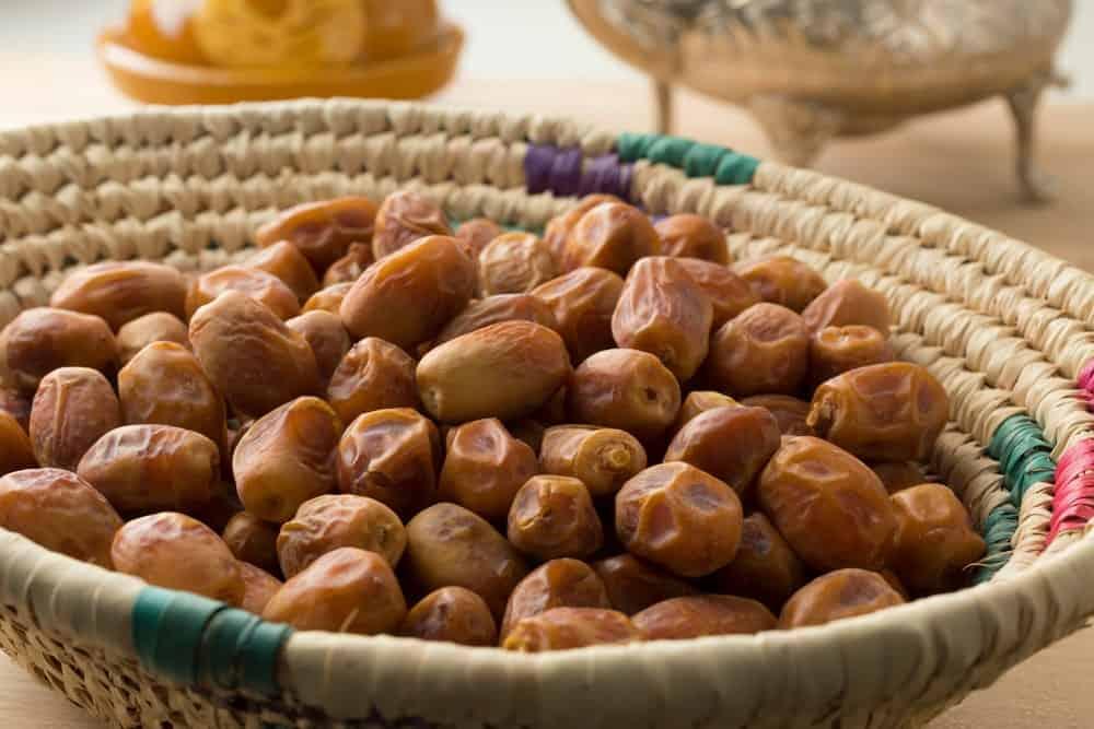 A heap of dried Zahidi Dates on a woven wicker basket.