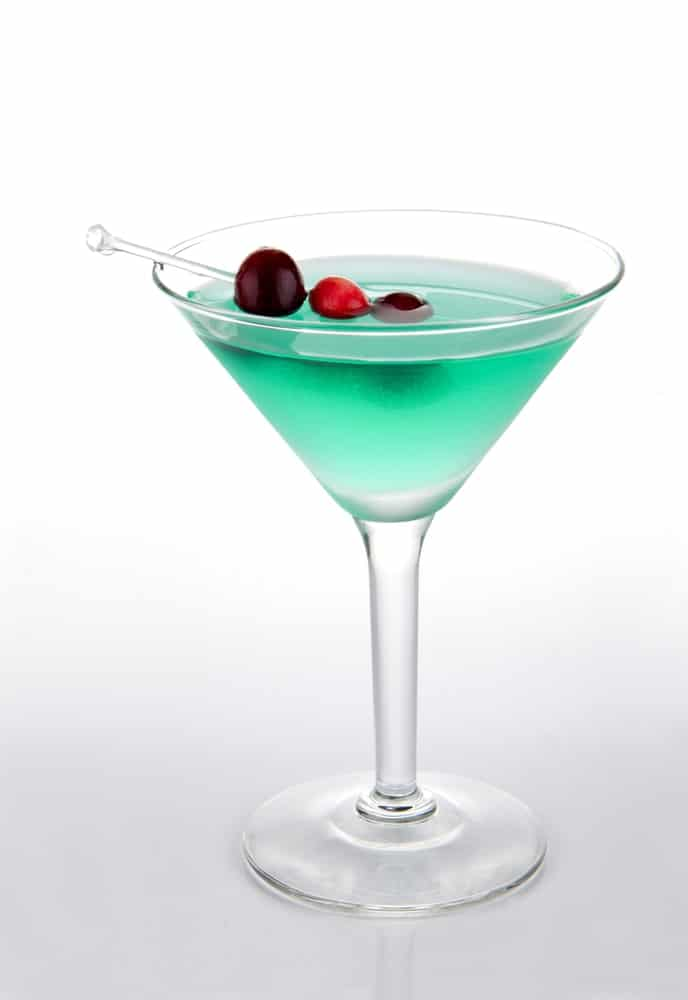 Green Martini bikini cocktail decorated with cranberries isolated on a white background.