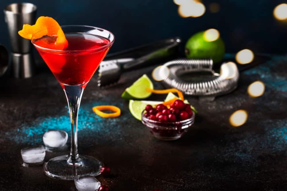 Classic alcoholic red cocktail cosmopolitan with vodka, liqueur, cranberry juice, lime, ice and orange zest on a dark bar counter background.