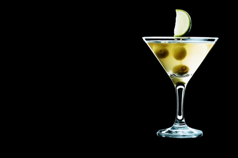 Dirty martini served with green olives and a slice of lime. A glass with cocktail isolated on a black background.