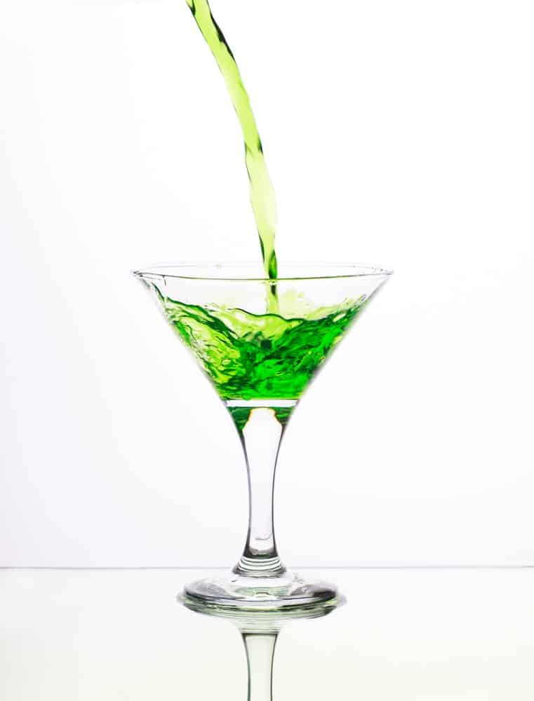 Emerald Martini pouring in a glass.