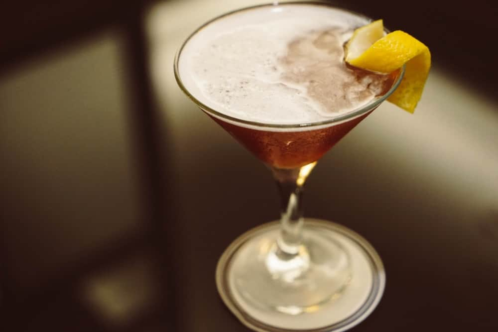French Martini with lemon peel on an upscale black countertop.
