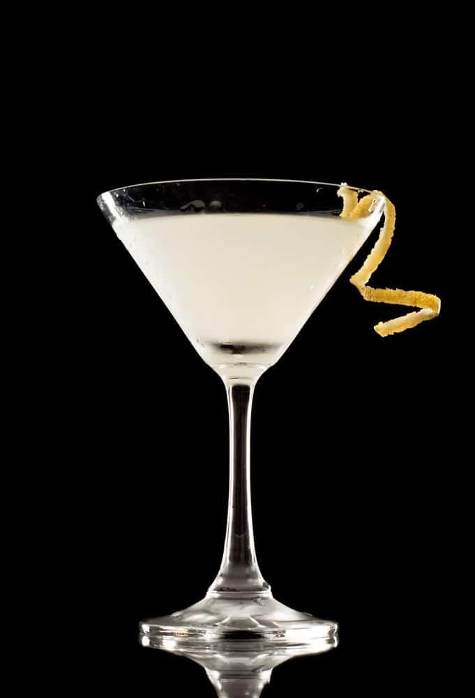 Shaken Martini over a black background garnished with a lemon twist.