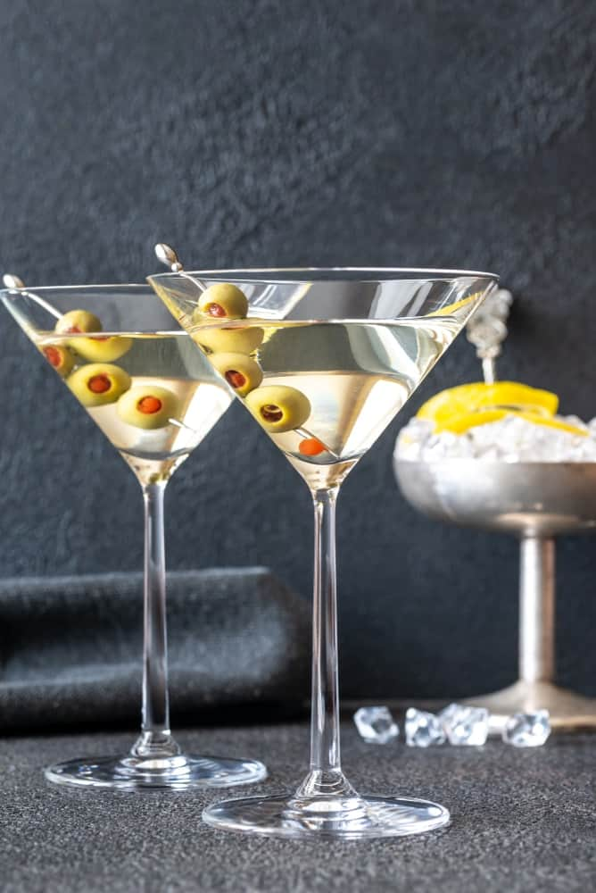Two glasses of vodka Martini with olives.