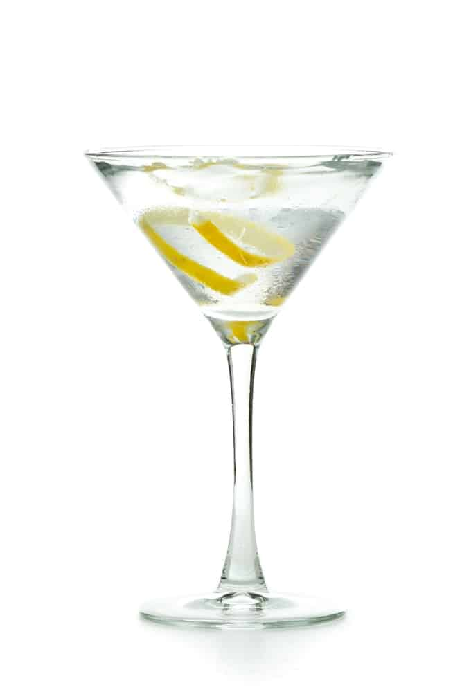 Vodka martini garnished with a lemon twist isolated on a white background.