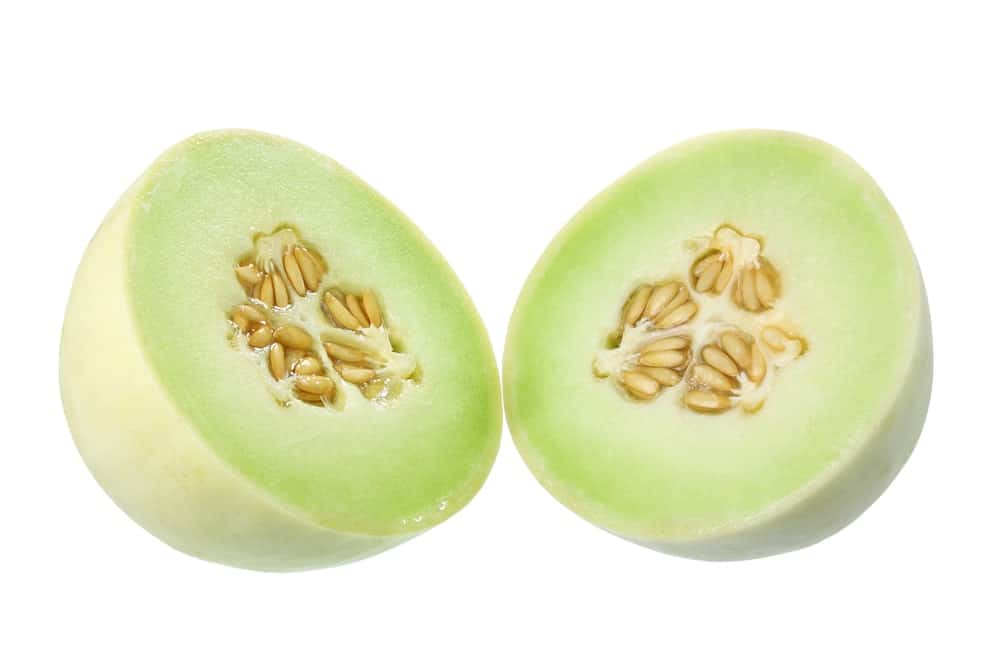 A Honeydew Melon cut in half to reveal its juicy insides.