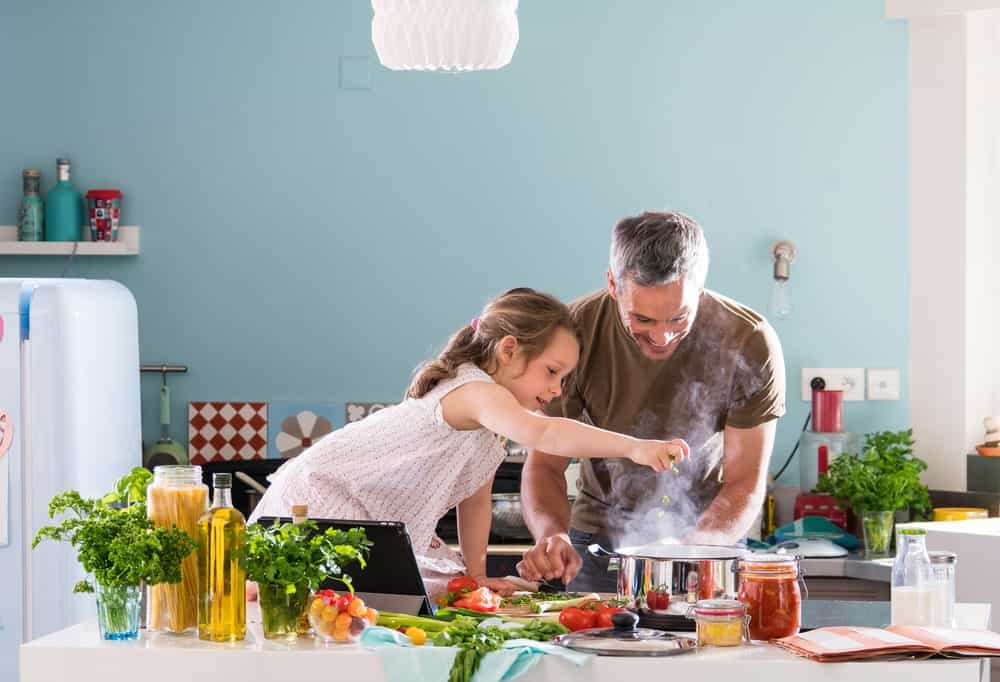 A father and daughter cooking in the kitchen.