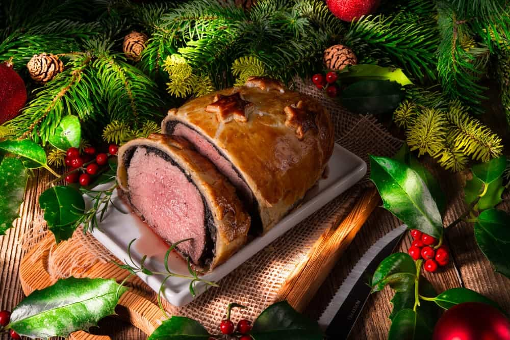 Beef Wellington surrounded by Christmas decorations.