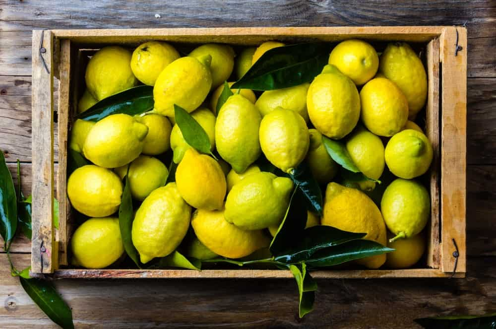 A crate full of lemons on a wooden background.