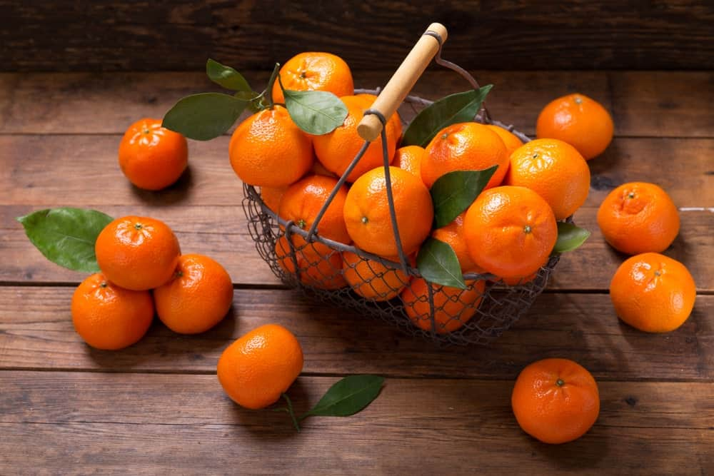 A wire basket full of tangerines surrounded by more tangerines on a wooden background.