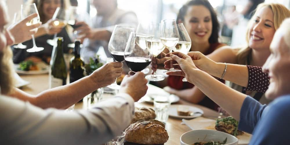 People at a dining table toasting with their wine glasses.