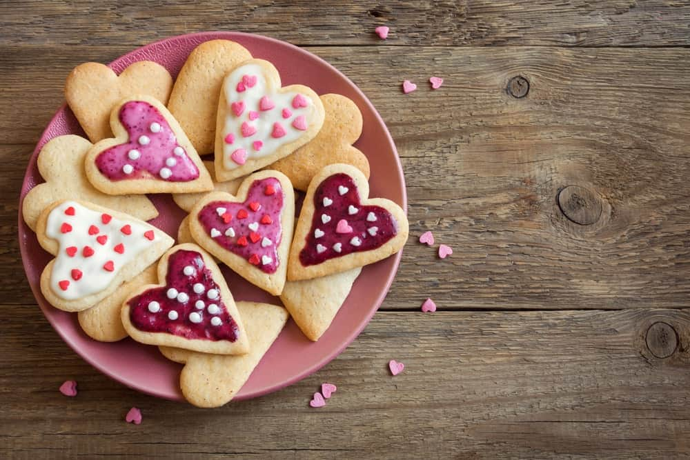 Heart cookies on a pink round plate on a wooden desk sprinkled with tiny pink hearts.