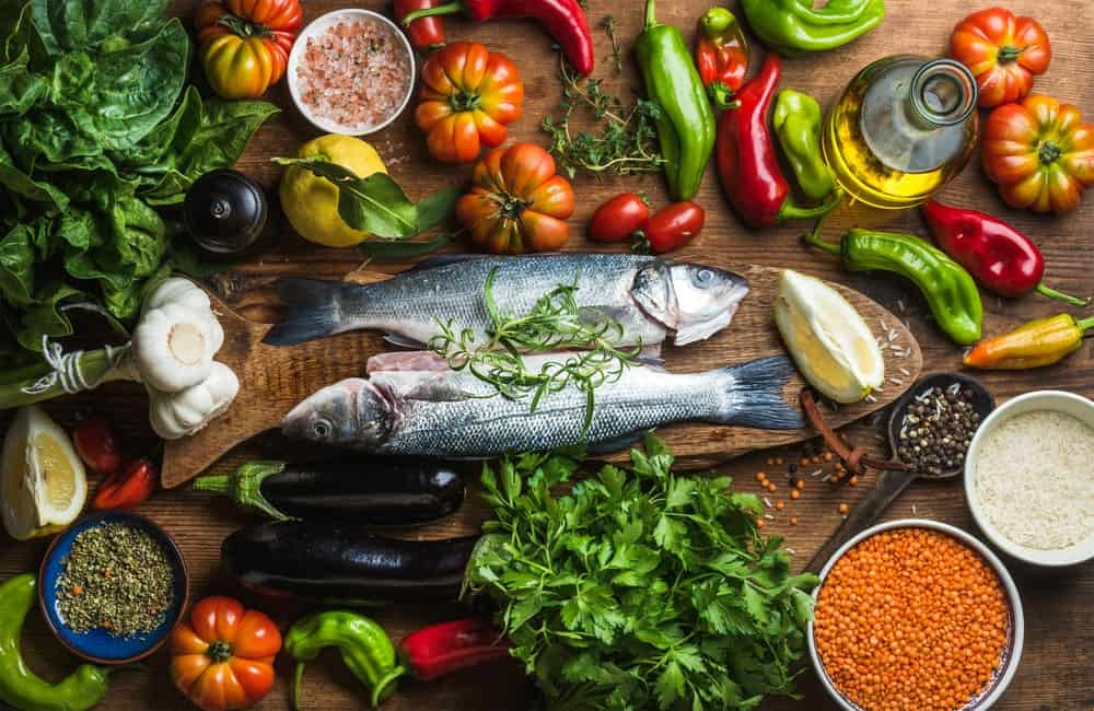 A variety of Mediterranean ingredients surrounding two raw fishes.
