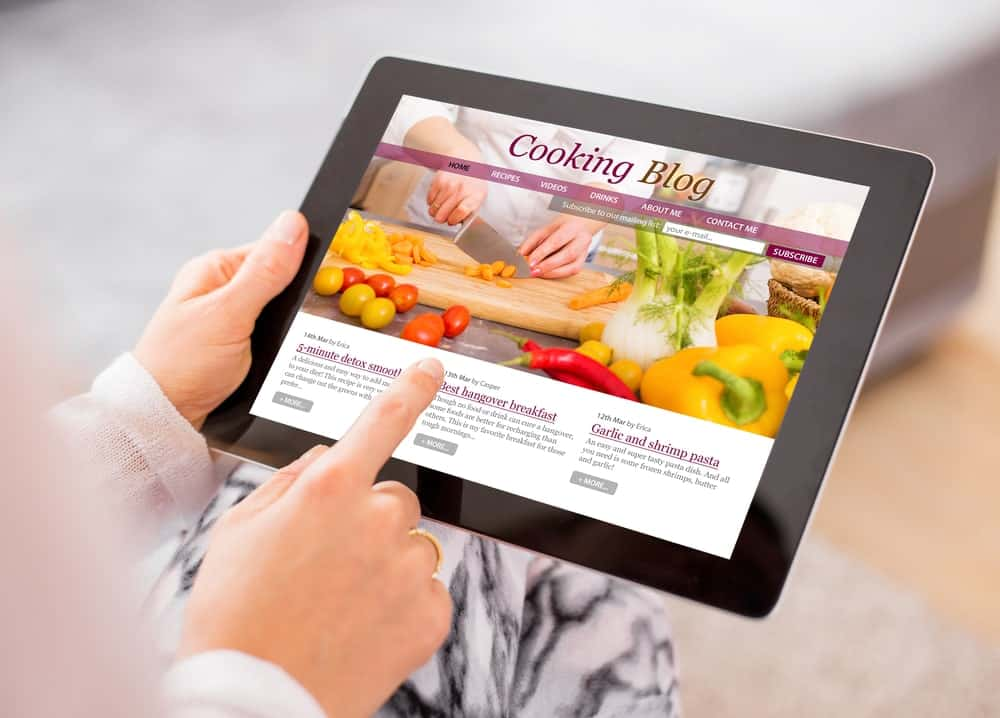Hands holding a tablet displaying a cooking blog onscreen.