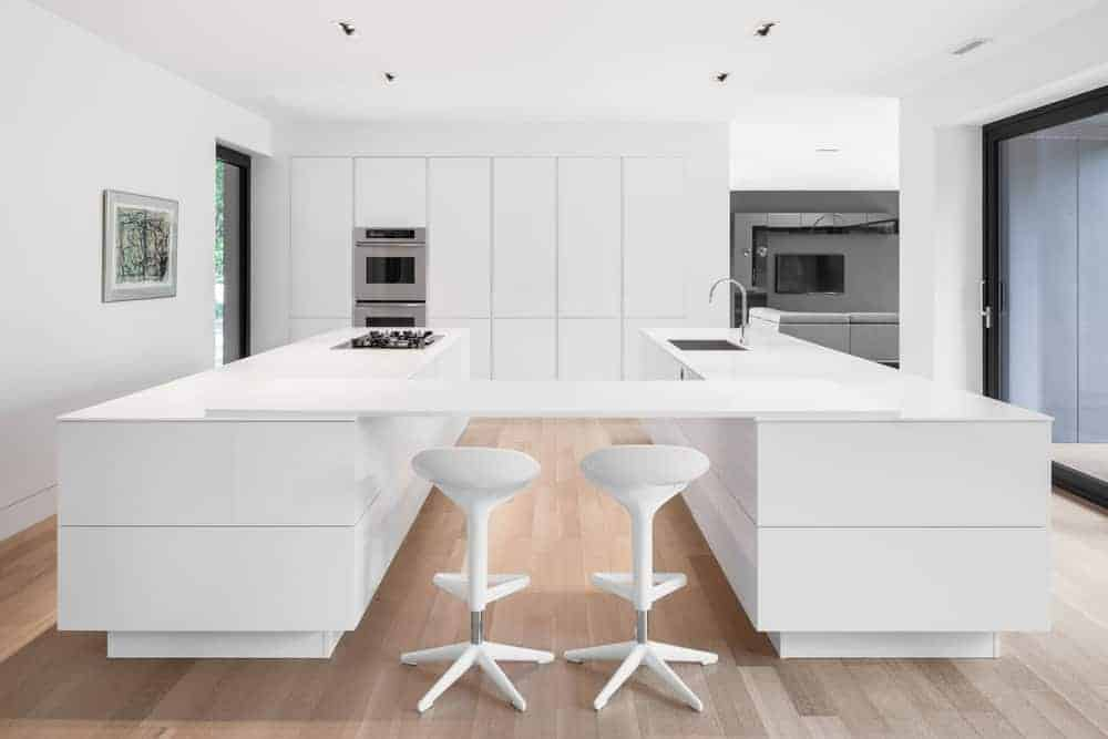 Going for an urban style kitchen? Take inspiration from this white minimalist kitchen, including the counter and barstools, with its double islands with built-in panel for a convenient dining table or additional kitchen top. The wooden flooring and the steel appliances go well with the whole white aesthetics.