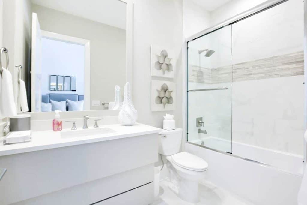 Looking for all-white bathroom designs? This might be the one you're looking for! The dominant color is white, which includes the toilet, the sink counter, and even the shower area, with just a touch of grey tiled ban design for a pop of color. It also has a medium-sized mirror by the sink.