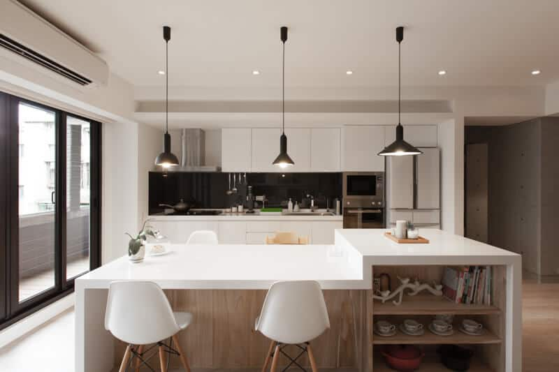 This modern kitchen has the right balance of class and function with its white kitchen counter and dining bar, paired with white chairs with wood and steel legs. The different-shaped black pendant lights provide sufficient lighting, aside from the natural sunlight allowed by the large glass doors. For good contrast, the bar frame and shelves, and the flooring are wood.