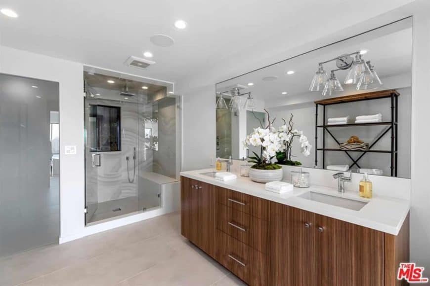 This bathroom has an Asian taste to it, particularly Japanese, with its dainty indoor flower atop a plain wooden sink and white counter, which matches the white glass-enclosed shower area with a small sitting area inside. The bathroom has wall lights that illuminate the large mirror right above the double sink.