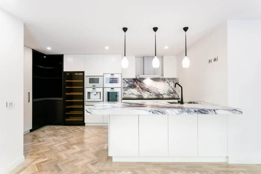 Spruce up your kitchen with the refreshing combination of marble countertop and faux wood flooring. Finish it off with a white pendant lighting for a classy touch.