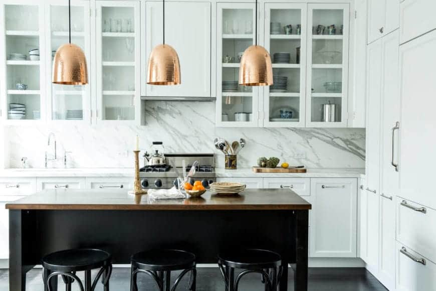 Going for a fancy home kitchen? Take a cue from this design. The marble splashback, white drawers, and dark wood dining bar go great together. For that sophisticated touch, you'll find fine-looking gold pendant lightings directly above the dining table, to light up the entire kitchen.