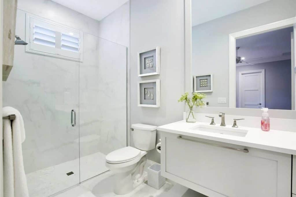 This bathroom offers nothing but the basic functions you'll need - it has a simple sink counter with a large mirror, a toilet, and an average-sized shower area enclosed in a glass door. For a personal touch, it shows a dainty flower vase on the counter, and some picture frames on the wall just above the toilet.