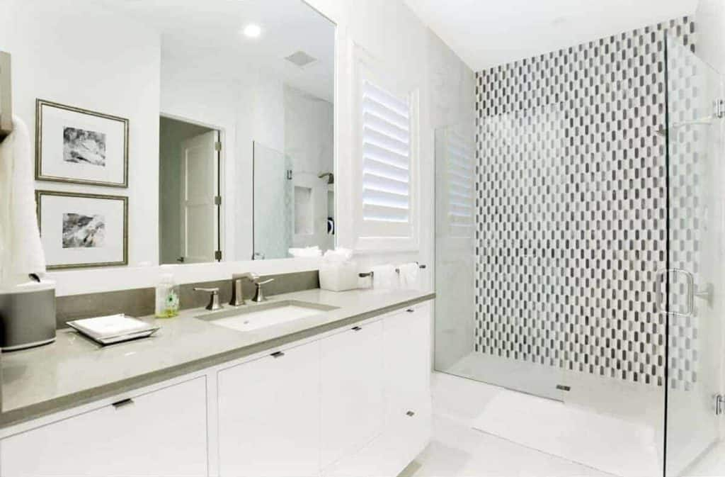 This stylish bathroom has marble countertop vanity and inset sink. This primary bath revolves around the clear glass paneling that encloses the huge walk-in shower.