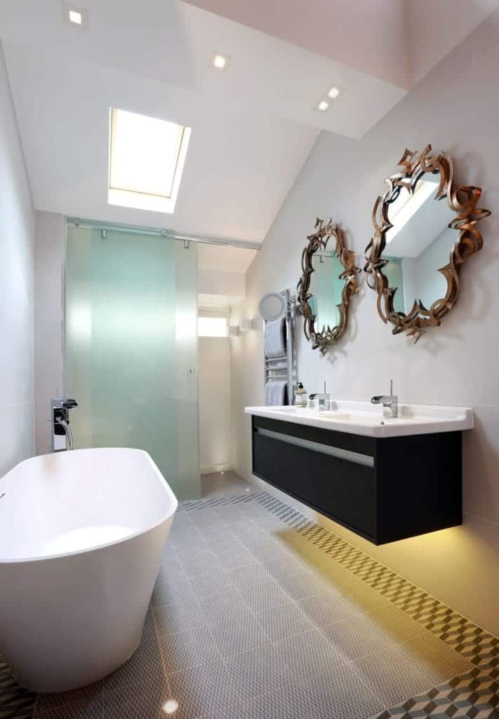 The modesty of the pure white walls and standard sized off white tiles complement the modern elements of the wall and white vaulted ceiling. This bathroom has stylish mirrors under the sink basin.