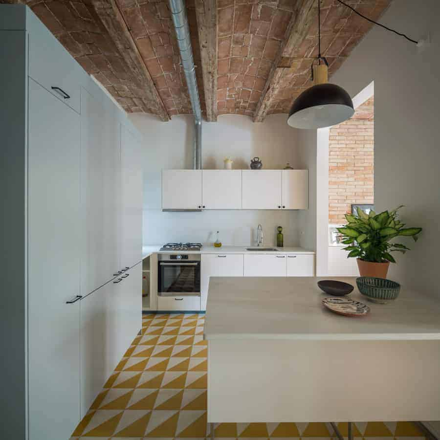 You can also go with mid-century modern kitchen design for a more homey feel. This kitchen has a simple white pantry and counter with a sink and oven. Its yellow and white tiled flooring gives the kitchen a nice touch of color.