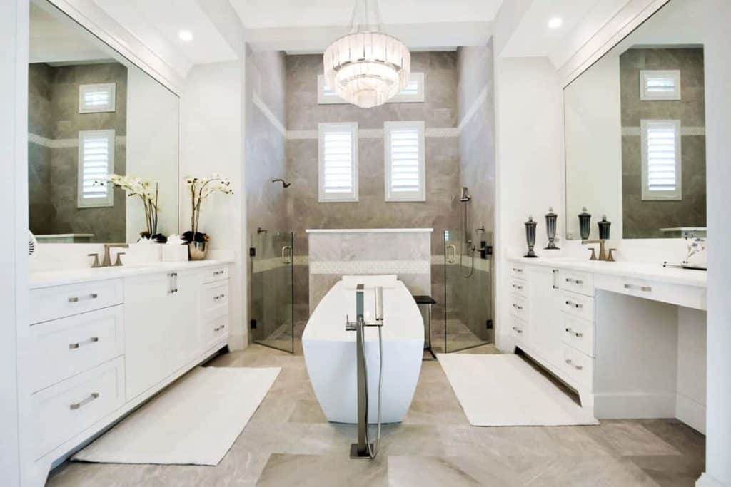 This large bathroom has a generous space for two, given its long counter with a sink on each side of the room, both with their individual bathroom essentials. Right in the middle is a white freestanding tub, with the large double shower behind it. To keep the room clean at all times, there are large white rugs on the marble tile flooring. The fancy 3-tier chandelier finishes the fancy look.