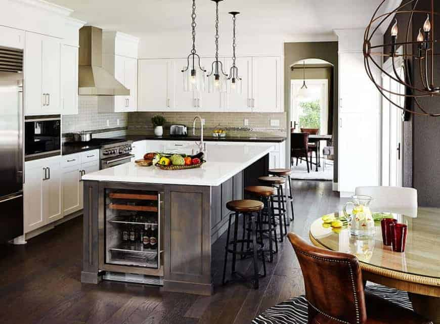 Fancy a country style kitchen? This kitchen can show you how! It has a dark wood island frame with a white countertop, which goes well with the hardwood flooring and the fancy brass pendant lights. Consider this an open kitchen with its smooth transition to the dining area.