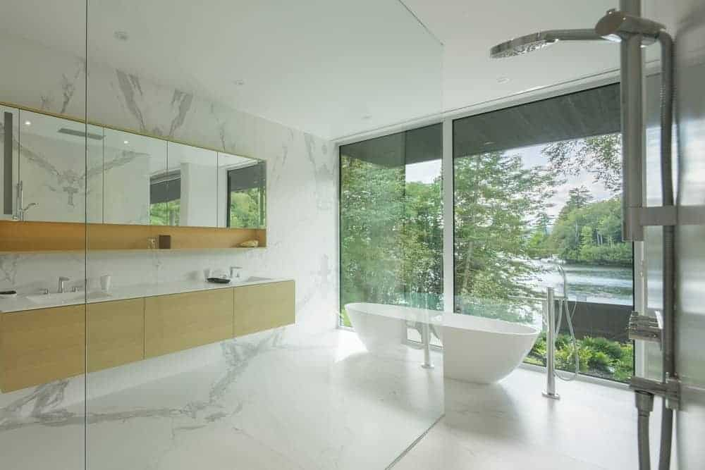 Small bathroom featuring double sink countertops match by white marble flooring. It also bathtub in the middle and a glass wall with a great view outside.