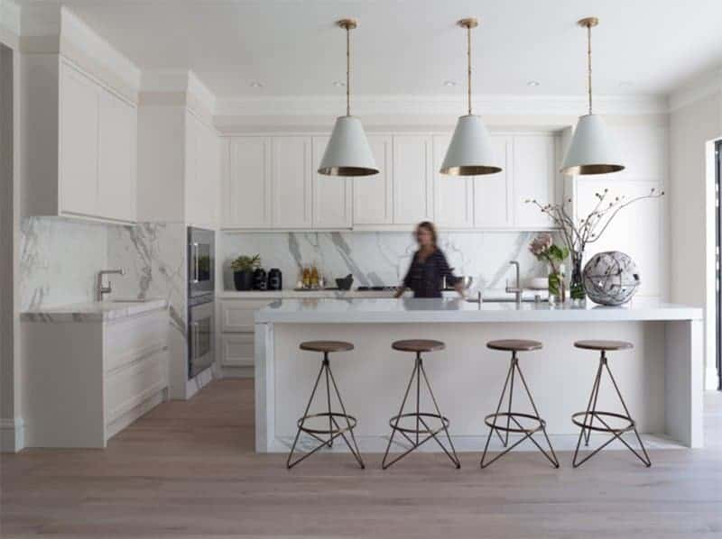 How about a Scandinavian inspired kitchen? This kitchen has a white island with built-in sink, marble splashback for a touch of color, and beautiful pendant lighting with gold tubing and canopies. The uniquely shaped bronze bar stools also go well with the dusty rose-coloured flooring.