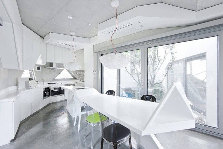 This kitchen has an eclectic design that goes perfectly if you like geometric shapes, like this white dining table with different colored chairs, with floral-shaped pendant lights above. It gives the entire room a bright look especially with the white counter with the appliances right under.