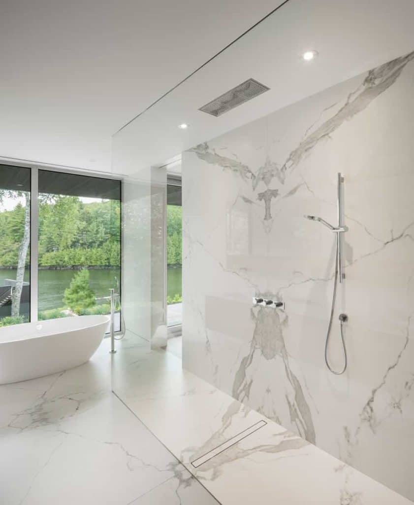 For a minimalist and functional design, you'll love this bathroom with its walk-in shower while sharing the open space with a freestanding tub. The marble flooring and walls, plus the recessed lights, give it a nice fancy touch without making it look over-the-top. The floor-to-ceiling glass window provides a refreshing view of the outdoors.