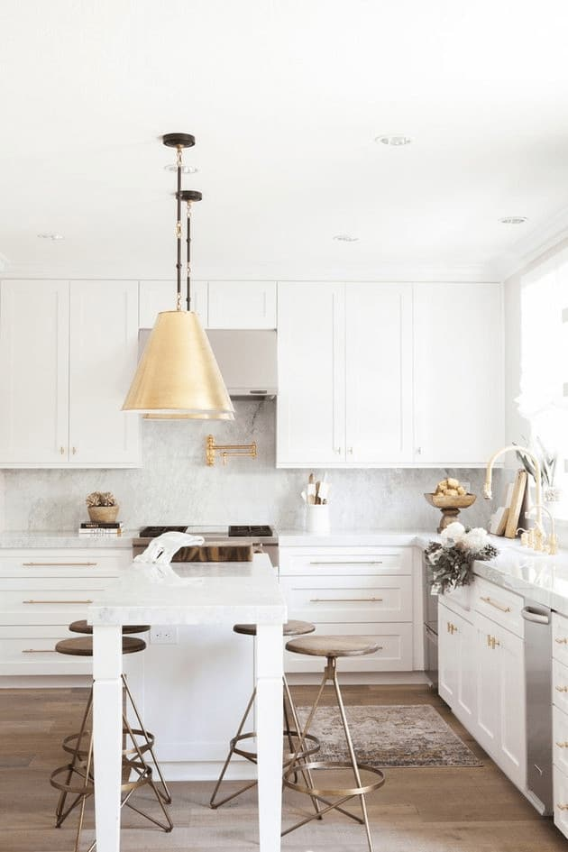 Go for a sophisticated touch in your kitchen with the perfect combination of white cabinetry and bronze bar stools for that subtle pop of color. It would also help to achieve a classy look with a brass pendant lighting, even a brass faucet and drawer handles.